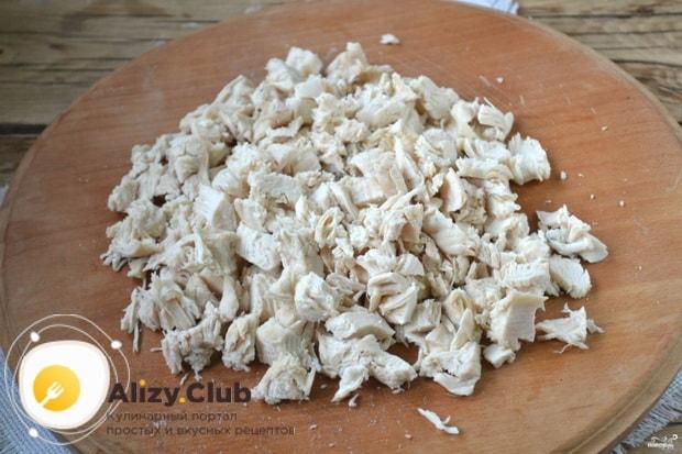 Нарежьте куриное филе для приготовления салата обжорка.