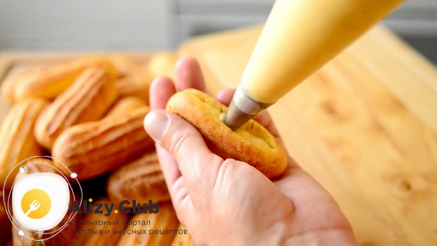 Для приготовления эклеров по простому рецепту, заполните заготовки кремом