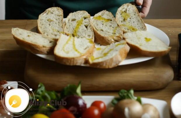 Для начала сбрызгиваем оливковым маслом тонко нарезанный хлеб.