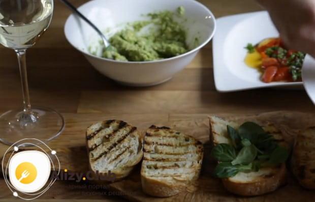 На поджаренные кусочки хлеба выкладываем листья салата.