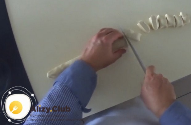 Тесто раскатываем в длинную колбаску и нарезаем ее на кусочки.