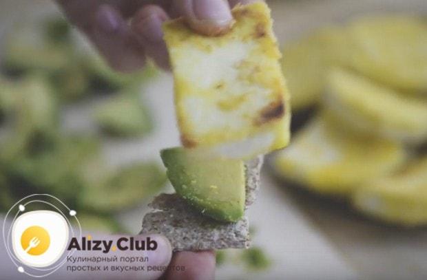 Собираем бутерброды, выкладываем на хлебцы кусочки авокадо и накрываем их обжаренным сыром.