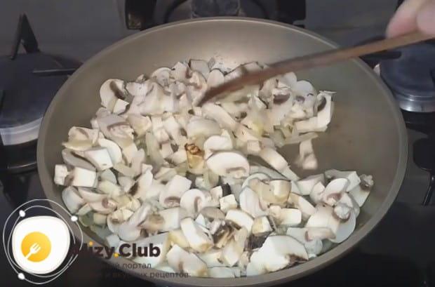 Добавляем грибы к луку на сковороду.