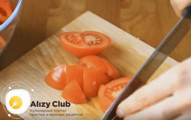 Небольшими кусочками режем помидор.