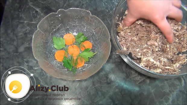 Берем пластиковый лоток и выкладываем на его дно несколько колечек моркови