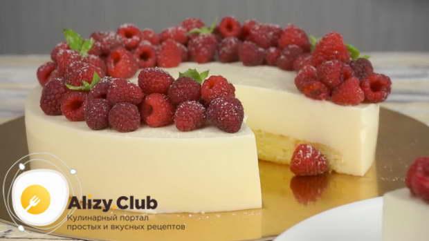 Перекладываем торт на подставку и украшаем ягодами малины