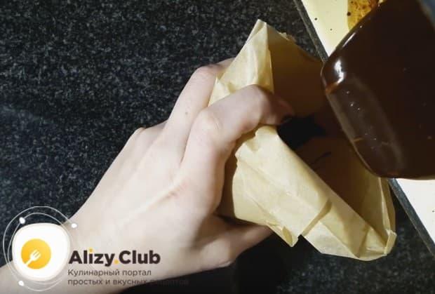 Переливаем готовую шоколадную массу в кондитерский мешочек или конвертик с маленьким отверстием.