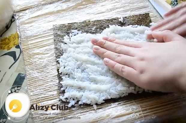 Смоченными в воде руками разравниваем рис тонким слоем по поверхности листа нори.