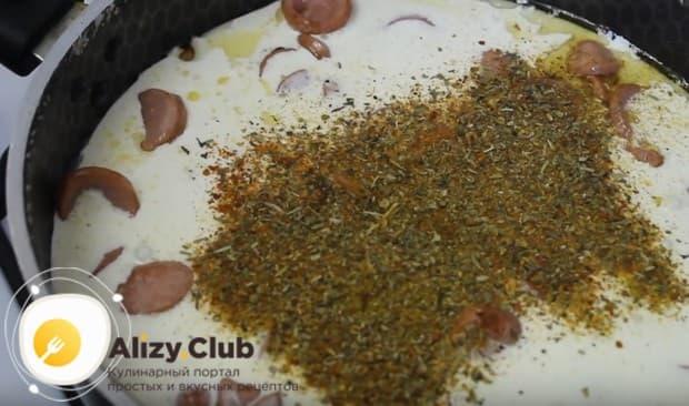 Заливаем сосиски сливками и добавляем специи.