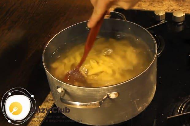 Насыпав макароны в кастрюлю, перемешиваем их.