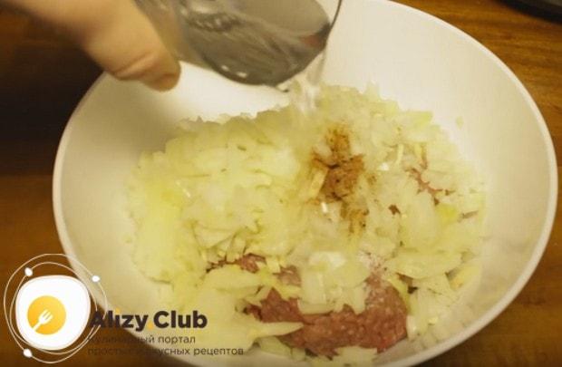 В мясной фарш выкладываем лук и чеснок, добавляем соль, перец и воду.
