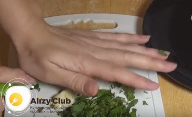 Измельчаем свежую зелень для украшения блюда, а также раздавливаем ножом и мелко режем чеснок.