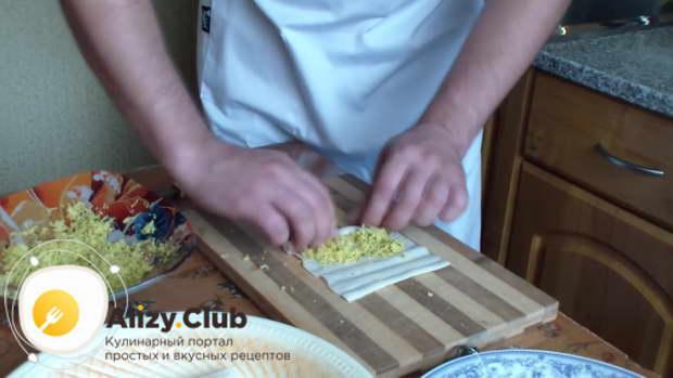 Сырную начинку выкладываем на развернутые крабовые палочки и каждую закручиваем рулетиком