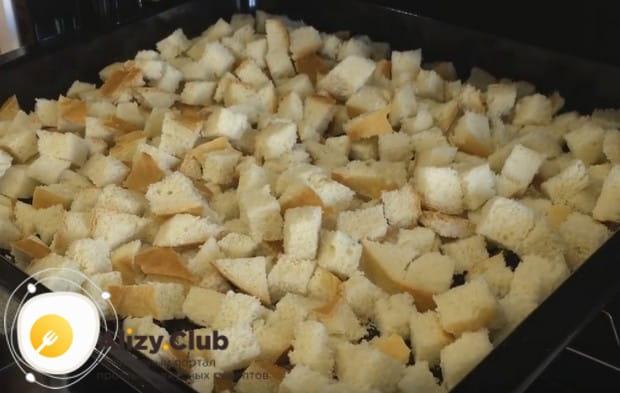 Подсушиваем кусочки хлеба на противне, чтобы получить светлые сухари.