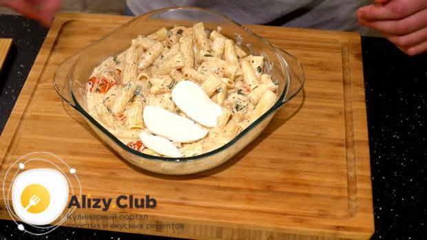 50 г моцареллы нарезаем на ломтики и выкладываем их в форму поверх макарон в соусе