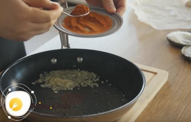В обжаренный лук добавляем молотый острый красный перец.
