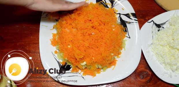 После этого раскладываем тертую морковь