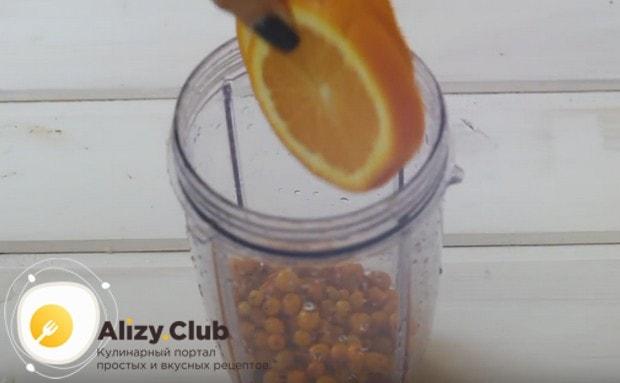 Половину ягод облепихи и апельсин складываем в чашу блендера.