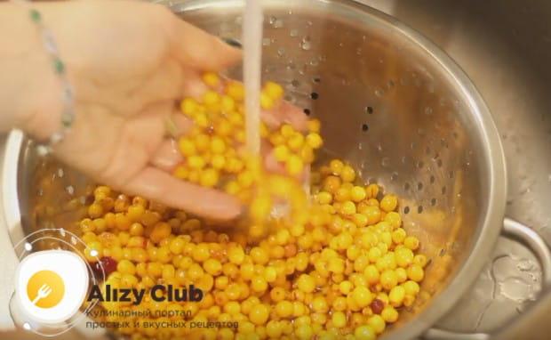 Перед тем, как приготовить облепиховый чай с апельсином, выкладываем облепиху в дуршлаг и промываем под проточной водой.