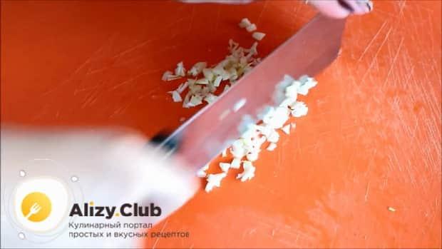 Для приготовления овощного рагу с кабачками в мультиварке, нарежьте чеснок.