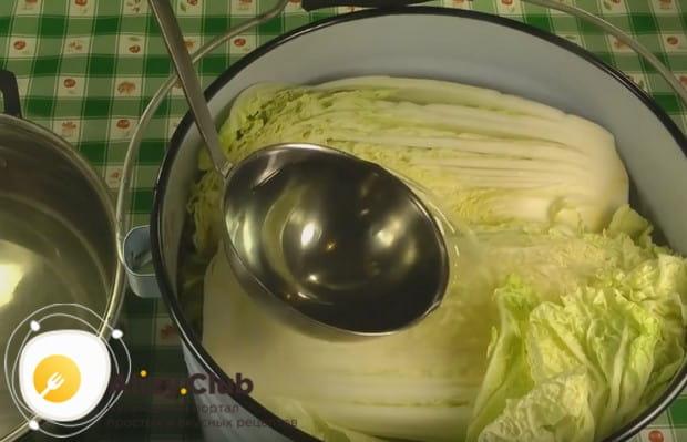Заливаем соленым раствором разрезанные пополам кочаны пекинской капусты.