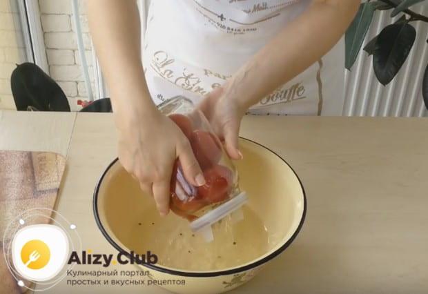 Сливаем воду с банок с помидорами.