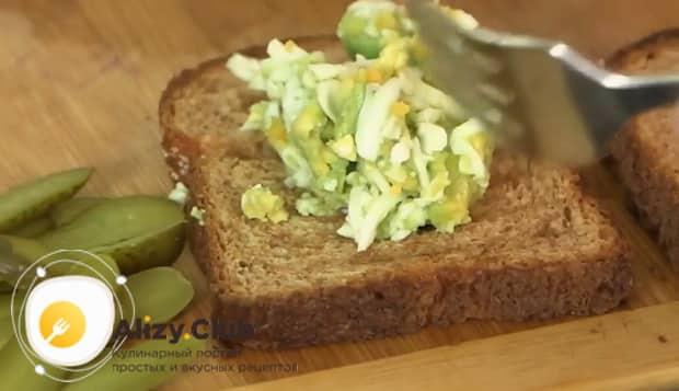 Выложите начинку на хлеб для приготовления вкусных бутербродов с печенью трески