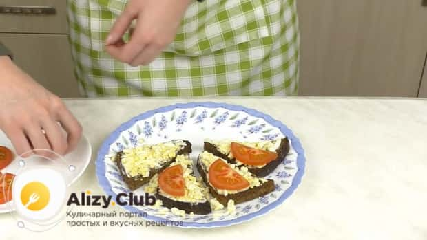 Для приготовления бутербродов со шпротами и помидорами выложите ингредиенты на хлеб.