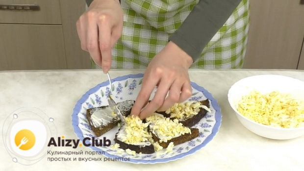 Для приготовления бутербродов со шпротами и помидорами выложите яйца на хлеб