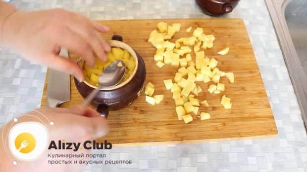 Для приготовления говядины с картошкой в духовке выложите картофель в горшочек