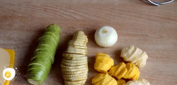 Для приготовления картошки с кабачками в духовке, нарежьте овощи