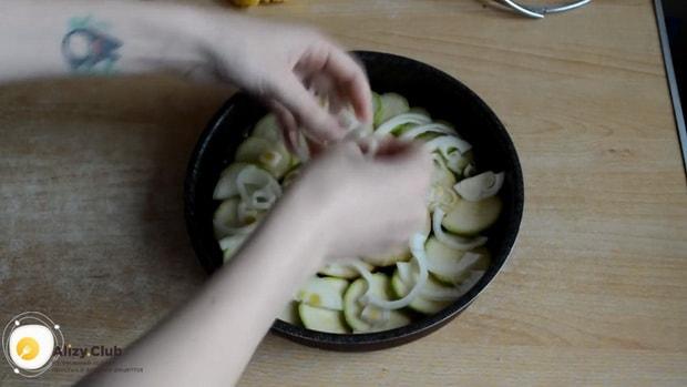 Для приготовления картошки с кабачками в духовке выложите лук