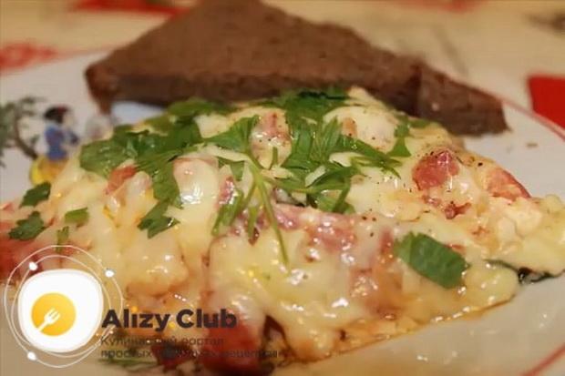 Вкусный омлет с помидорами и колбасой на сковороде готов.
