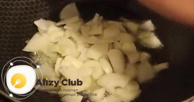 Для приготовления омлета с помидорами и колбасой на сковороде, обжарьте лук.