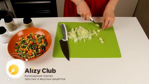 Для приготовления риса с замороженными овощами на сковороде нарежьте лук и чеснок