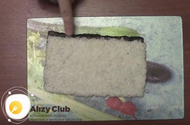 Плотным тонким слоем выкладываем рис на лист нори, оставляя тоненькую полоску с одного края.