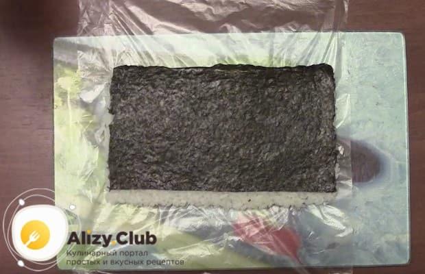 Обратная сторона листа нори должна быть пустой, только с одного края делаем тонкую полоску риса.