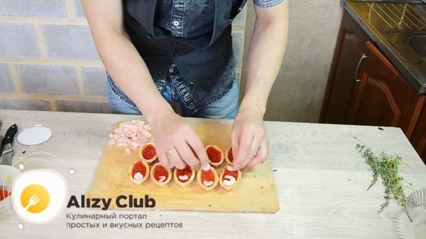 Для приготовления тарталеток с красной икрой по лучшему рецепту, нарежьте морепродукты