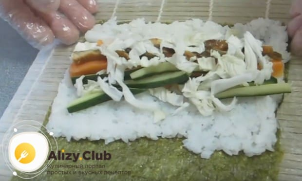 затем выкладываем кусочки огурца, красной рыбы и угря, китайской капусты.