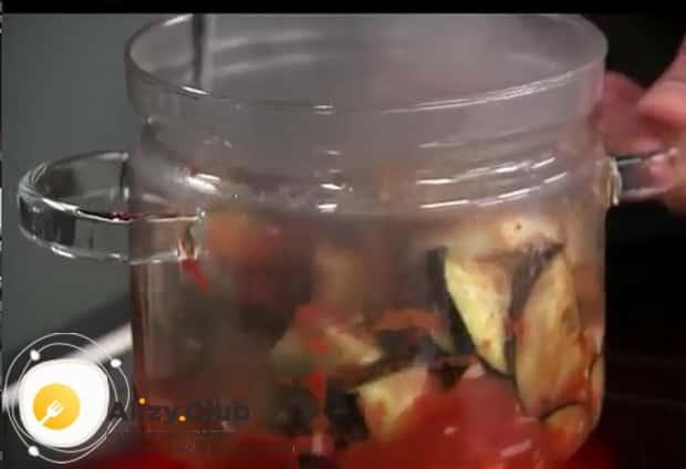 Выложите ингредиенты в банку для приготовления баклажанов в томатном соусе по простому рецепту.