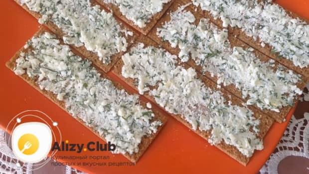 Для приготовления закуски из лаваша с красной рыбой, по простому рецепту смажьте хлебцы