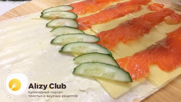 Для приготовления закуски из лаваша с красной рыбой, по простому рецепту положите огурцы