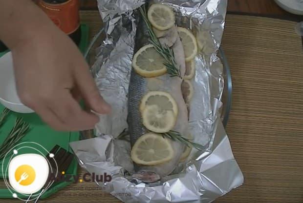 Поверх рыбы тоже кладем кусочки лимона и веточки розмарина.