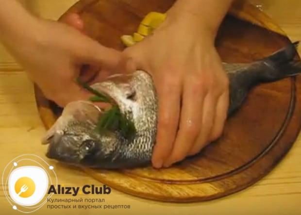 Внутрь рыбину кладем несколько веточек свежей зелени и кусочки лимона.