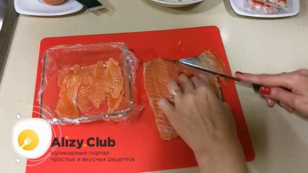 По рецепту для приготовления салата суши, нарежьте рыбу.