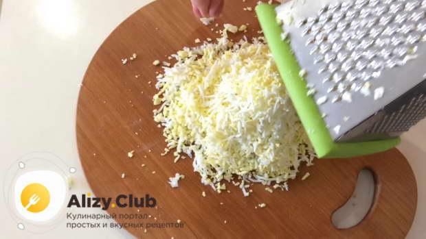 На средней терке натрите вареные яйца, переложите на тарелку
