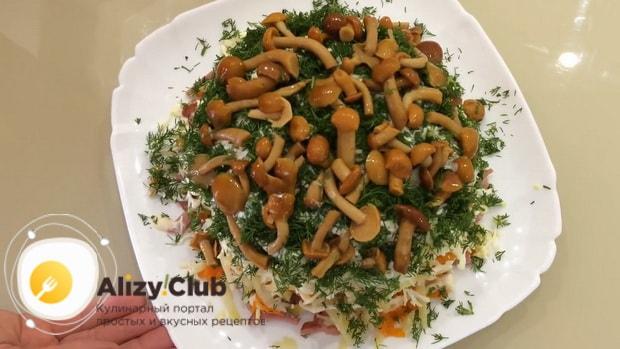 Для пригготовления салата с маринованными опятами и курицей, украсьте грибами и зеленью