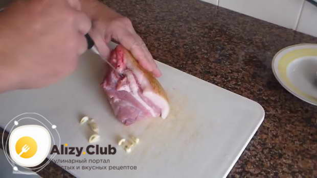 Сделайте в куске сала небольшие отверстия ножом и нашпигуйте их чесноком