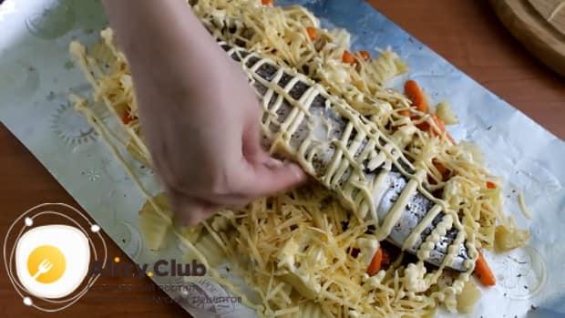 Для приготовления скумбрии запеченная в фольге в духовке, посыпьте рыбу сыром