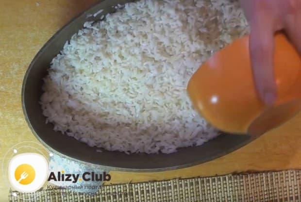 Выкладываем рис и поливаем его растопленным сливочным маслом.
